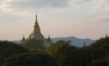 Perhaps the highest revered temple in Bagan, the Ananda Pagoda was built in 1105 CE during the reign of King Kyanzittha (1084–1113) of the Bagan Dynasty. It is one of four surviving original temples of Bagan (also called Pagan). The temple layout is in a cruciform with several terraces leading to a small pagoda at the top covered by an umbrella ('hti').<br/><br/>  The Buddhist temple houses four standing Buddhas—facing east, north, west and south. The temple is said to be an architectural wonder in a fusion of Mon and adopted Indian styles of architecture.<br/><br/>  It was damaged in the earthquake of 1975. However, it has been fully restored and is well maintained by frequent painting and whitewashing of the walls. On the occasion of the 900th anniversary of its construction celebrated in 1990 the temple spires were gilded.<br/><br/>  Bagan, formerly Pagan, was mainly built between the 11th century and 13th century. Formally titled Arimaddanapura or Arimaddana (the City of the Enemy Crusher) and also known as Tambadipa (the Land of Copper) or Tassadessa (the Parched Land), it was the capital of several ancient kingdoms in Burma.
